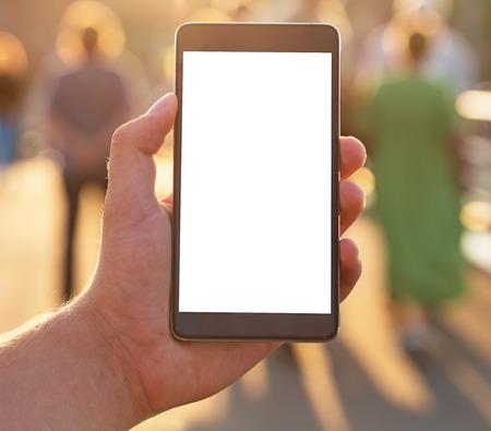 Man gebruikt zijn mobiele telefoon buiten, close-up. Man met behulp van mobiele slimme telefoon met leeg wit scherm.