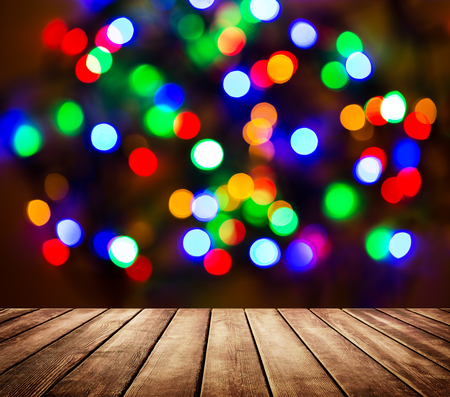Empty wooden table in front of abstract blurred background with light spots and bokeh. Multicolor abstract bokeh background.
