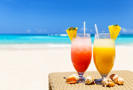 Two tropical fresh juices on white sandy beach in Punta Cana, Dominican Republic