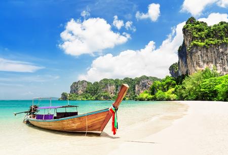 Tajska tradycyjna drewniana łódź typu longtail i piękna piaszczysta plaża Railay w prowincji Krabi. Ao Nang, Tajlandia.