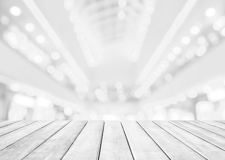 Abstract blur shopping mall background. Abstract shopping mall and retails store interior for background with bokeh light. Empty wooden table over blurred store with bokeh light. Zdjęcie Seryjne