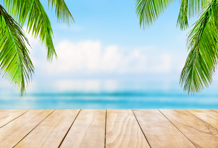 Wooden table top on blue sea and white sand beach background. Coconut palm trees against blue sky and beautiful beach in Punta Cana, Dominican Republic. Vacation holidays background wallpaper.