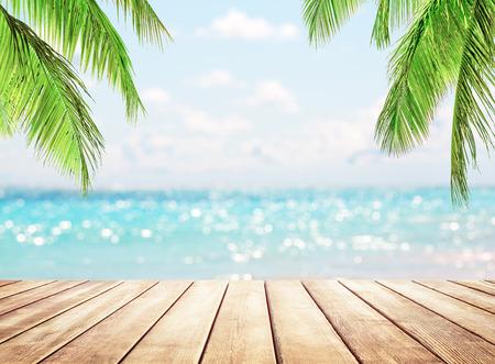 Piano del tavolo in legno sul mare blu e sullo sfondo della spiaggia di sabbia bianca. Palme da cocco contro il cielo blu e la bellissima spiaggia di Punta Cana, Repubblica Dominicana. Sfondo vacanze vacanze.