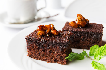 Chocolate cake with mint leaf on white plate on table.