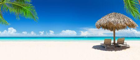 Strandkörbe mit Sonnenschirm und schönem Sandstrand in Punta Cana, Dominikanische Republik. Panorama des tropischen Strandes mit weißem Sand und türkisfarbenem Wasser. Reisen Sie Sommerurlaub Hintergrundkonzept.