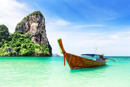 Thai traditional wooden longtail boat and beautiful sand Railay Beach in Krabi province in Thailand. Ao Nang, Thailand.