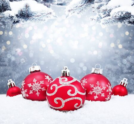 Beautiful red Christmas balls on the red background. Christmas ornament on snow with fir branches.