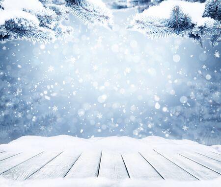 Zimowe dekoracyjne świąteczne tło z bokeh światła, płatki śniegu i pusty stary drewniany stół. Boże Narodzenie i szczęśliwego nowego roku niebieskie tło z płatka śniegu. Zimowy krajobraz z padającego śniegu i gałęzie jodły.