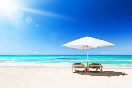 Beach chairs with white umbrella and beautiful sand beach in Punta Cana, Dominican Republic.