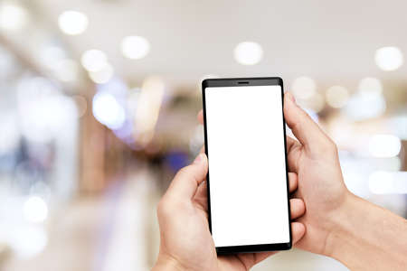 Man`s hand holding mobile smart phone with blank screen at blurred shopping mall background. 스톡 콘텐츠