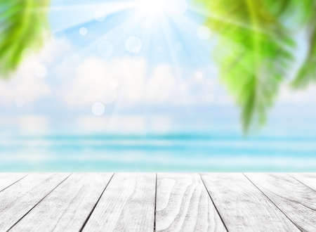 Blurred blue sky and sea with bokeh light and leaves of coconut palm tree. Landscape of tropical summer. Summer vacation concept. 스톡 콘텐츠