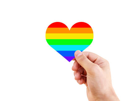 Lgbt flag rainbow heart shape on white. Man hand holding a heart painted like a LGBT flag isolated on a white background.