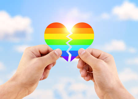 Two gay men holding a heart painted like a LGBT flag against sunny blue sky background. Lgbt flag rainbow heart shape on blue sky background. 스톡 콘텐츠