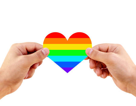 Two gay men holding a heart painted like a LGBT flag, isolated on a white background. Lgbt flag rainbow heart shape on white background. 스톡 콘텐츠