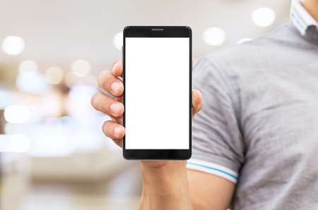 Man holding mobile smart phone with blank screen at blurred shopping mall background.