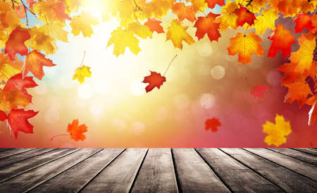 Wooden table top on blur autumn background. Autumn golden abstract background with bokeh light and colorful fall leaves.