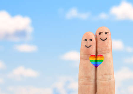 A happy gay couple in love with painted smiley and one heart for two. Two gay fingers with a heart painted like a LGBT flag against sunny blue sky background.