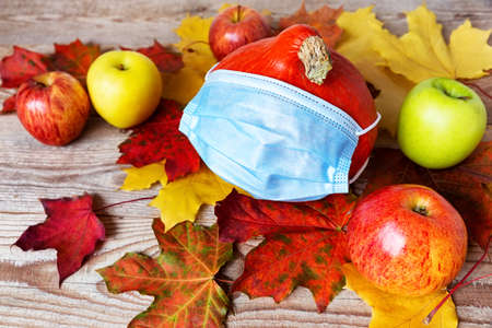 A mask on autumn pumpkin with colorful leaves, healthcare and hygiene concept. Halloween autumn concept with corona virus prevention. 스톡 콘텐츠