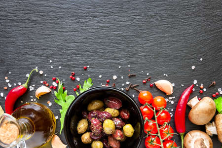 Food ingredients on dark background. Tomatoes, spices, garlic, mushrooms and basil leaves on black background. Vegetarian food, health or cooking concept.