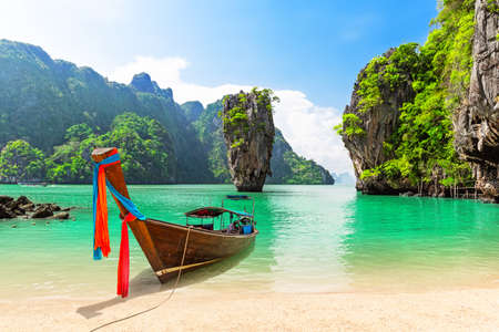 Famous island near Phuket in Thailand. Travel photo of island with thai traditional wooden longtail boat and beautiful sand beach in Phang Nga bay, Thailand.