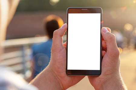 Man uses his Mobile Phone outdoor, close up. Mockup image blank white screen cell phone. Men hand holding texting using mobile phone outdoor. Imagens