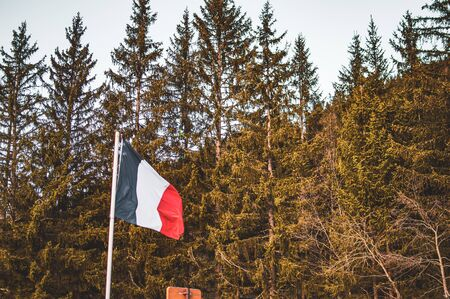 picture of a french flag flapping in a wind. Mountains behind the flag, snow on m ountains, French alps. 版權商用圖片