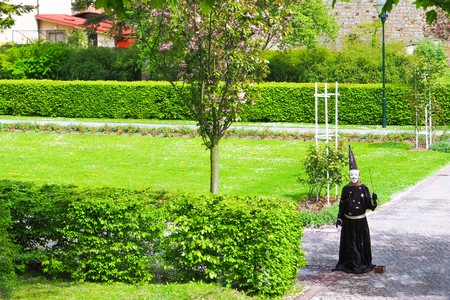 sorcery: A man dressed in a mask and wizard gown holding magic wand standing in a park near blooming tree in spring.