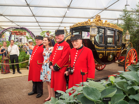 keywords: LONDON, UK - MAY 25, 2017: RHS Chelsea Flower Show 2017. Chelsea Pensioners pose with a young woman visitor near the Australian State Coach in the Great Pavillion. Editorial