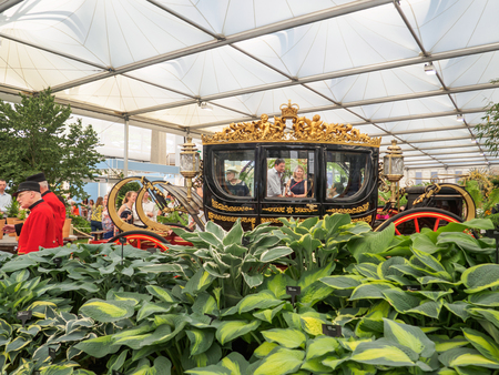LONDON, UK - MAY 25, 2017: RHS Chelsea Flower Show 2017. Visitors observing the Australian State Coach standing near the Bowdens hostas in the Great Pavillion.