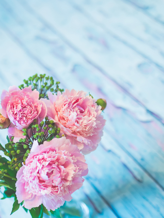 A bouquet of beautiful pink peonies on a bluish rustic wooden table shot against soft-focused background.