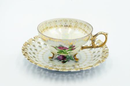 Tazza da tè vintage in porcellana con decorazione a linea dorata e piattino intagliato, sfondo bianco