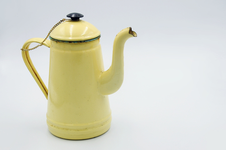 Vintage enamel pitcher is a pale yellow on white backgound, Place for text Stock fotó
