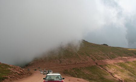 Mountain dirt road with cars and fog on an cloudy day Stock Photo