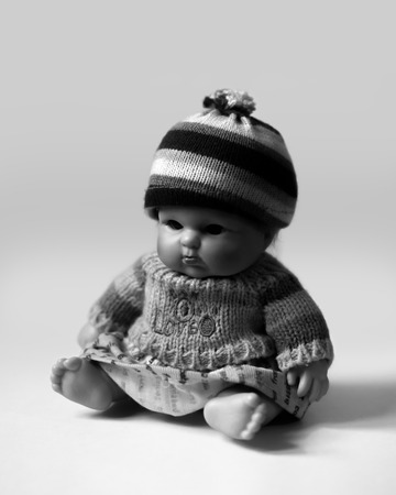 BLACK AND WHITE PHOTO OF SITTING DOLL