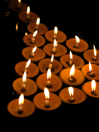 OFFERING LIT CANDLES Stock Photo