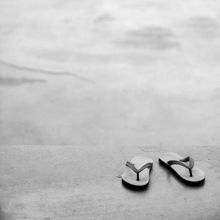 BLACK AND WHITE PHOTO OF PAIR OF FLIP FLOPS ON CONCRETE GROUND