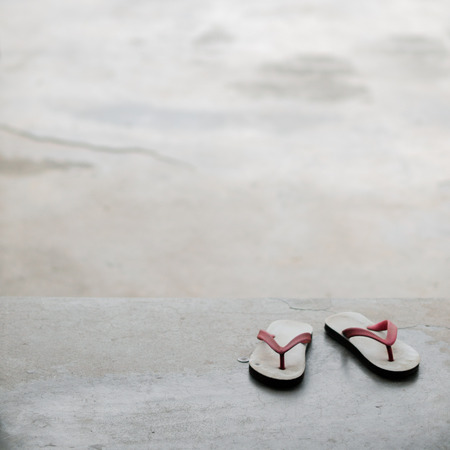 y shaped: COLOR PHOTO OF PAIR OF FLIP FLOPS ON CONCRETE GROUND Stock Photo