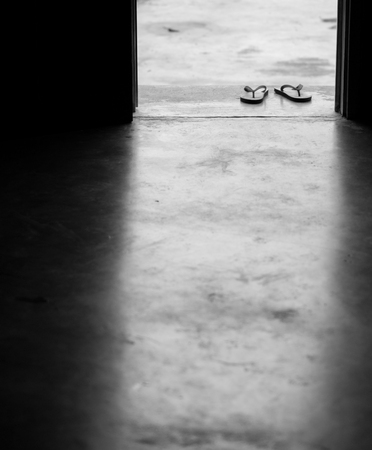y shaped: BLACK AND WHITE PHOTO OF PAIR OF FLIP FLOPS ON CONCRETE GROUND