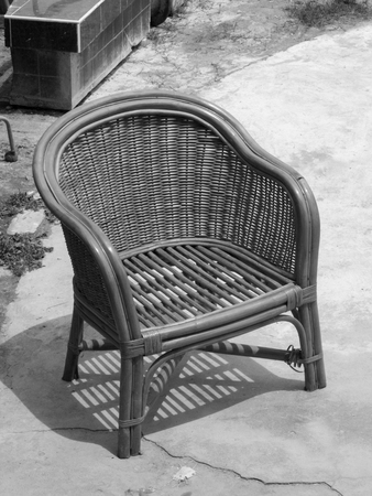 sitting on the ground: BLACK AND WHITE PHOTO OF RATTAN CHAIR ON CONCRETE GROUND