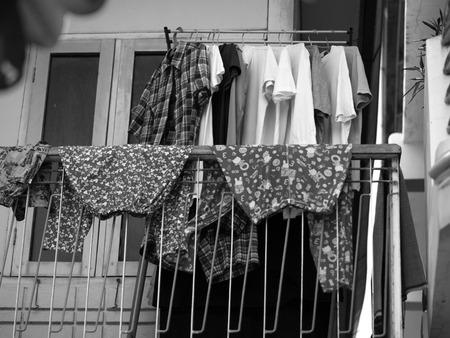 hangers: BLACK AND WHITE PHOTO OF CLOTHES DRYING ON THE BALCONY Stock Photo