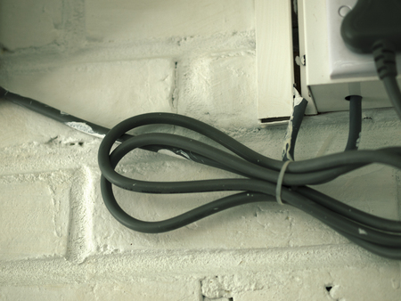 cable tangle: COLOR PHOTO OF ELECTRICAL CABLE ON WHITE BRICK WALL