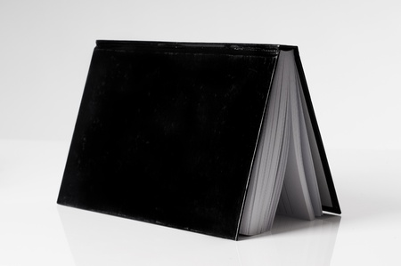 black book open on a white table for cutout photo