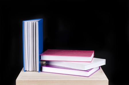 four colorful books on a wooden table on a black background photo