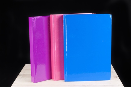 three colorful books on a black background photo