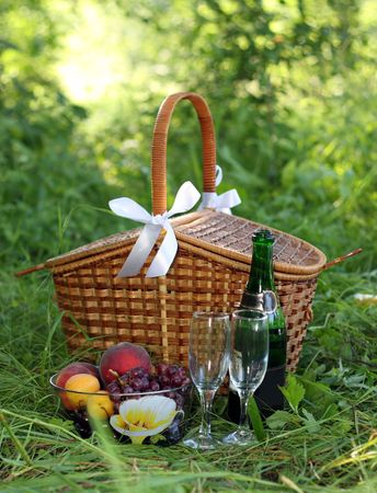 basket for picnic with champagne and fruits Archivio Fotografico