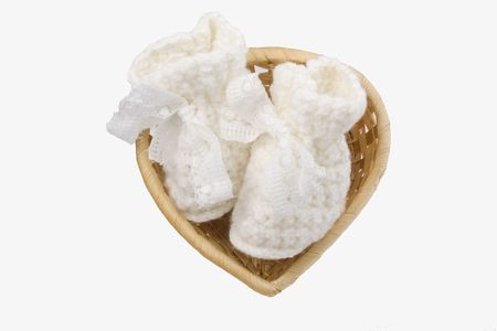 baby's bootee: wicker basket heart-shaped with babys bootee on white background