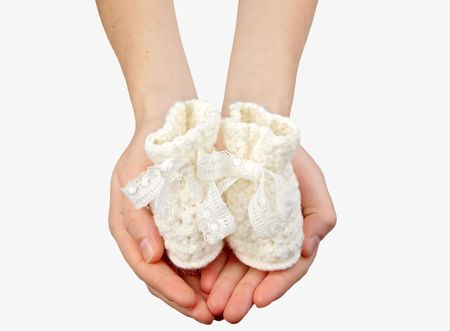 womans hands with babys bootee photo