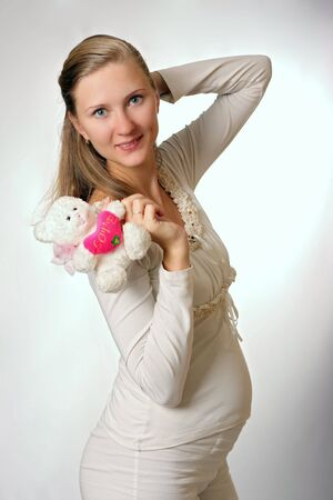 fruition: happy pregnant woman with toy on white background Stock Photo