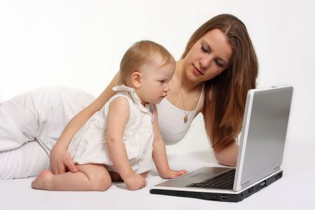 beautiful mother with daughter looking on the laptop photo