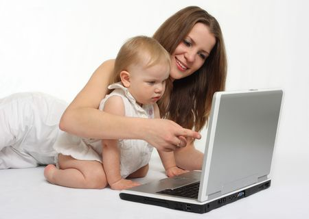 beautiful mother with daughter looking on the laptop